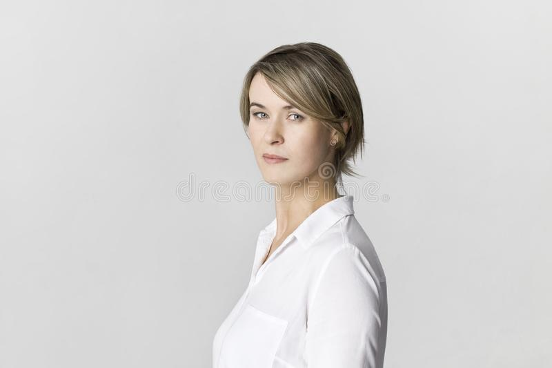 Serious businesswoman in white shirt portrait against white wall stock image