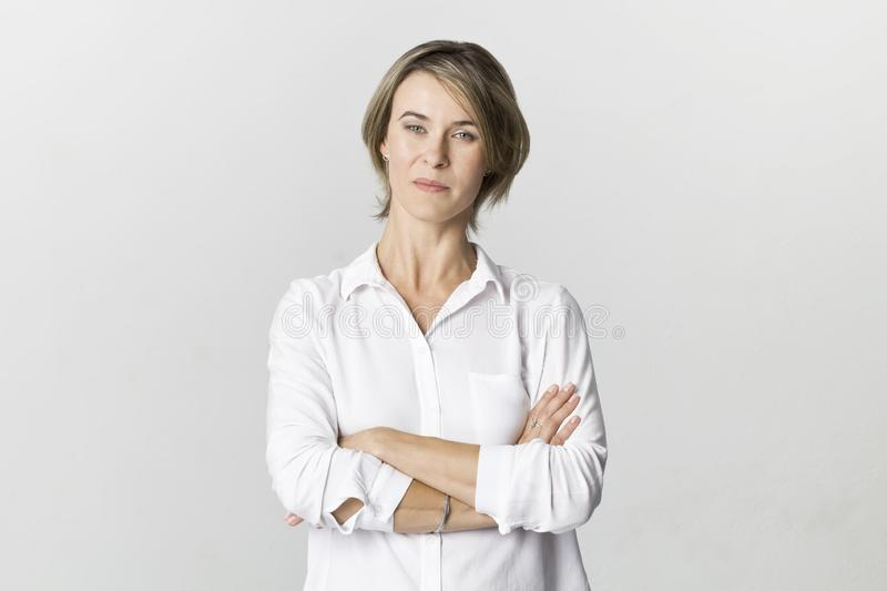 Serious businesswoman standing with arms crossed. Confidence woman in white shirt isolated on white royalty free stock photos