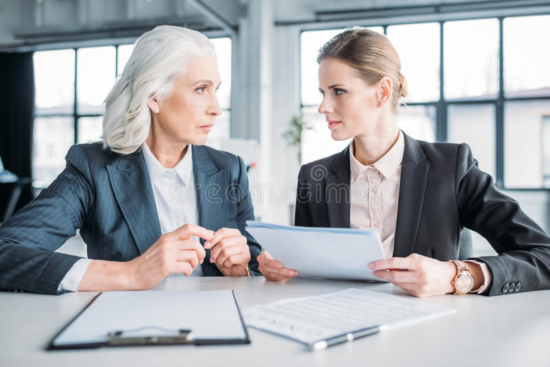 Serious businesswomen with documents discussing business project on meeting in office stock photos