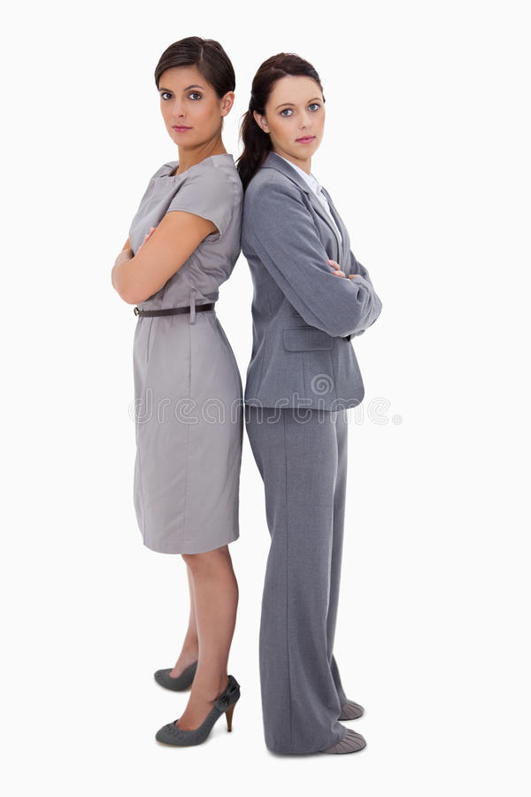 Serious businesswomen standing back on back