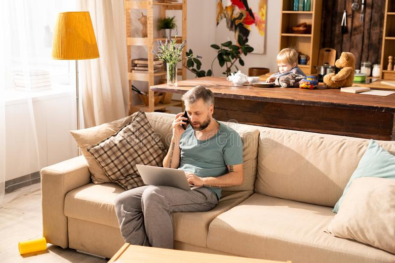 Busy father working at home while son being bored stock photos