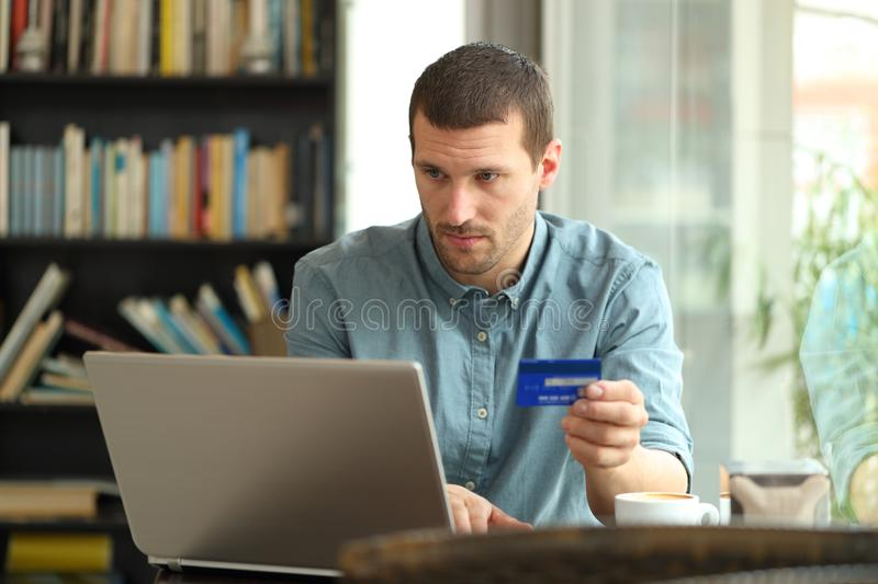 Serious buyer buys with credit card and laptop in a bar. Serious buyer buys with credit card and laptop sitting in a coffee shop stock image
