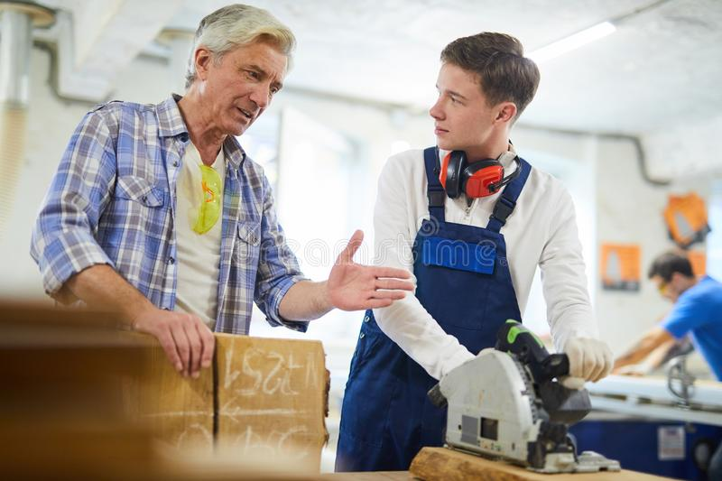 Serious carpenter giving advice to intern in workshop stock photo