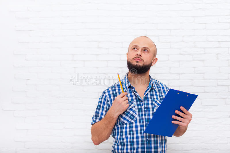 Serious Casual Bearded Business Man Holding Folder Look To Copy Space Pondering Doubtful royalty free stock image