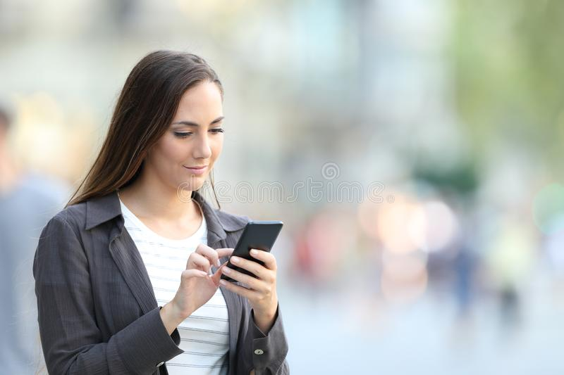 Serious female browsing phone content in the street stock image