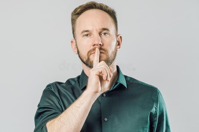 Serious caucasian man holding index finger over mouth saying shh. Over gray background royalty free stock photos