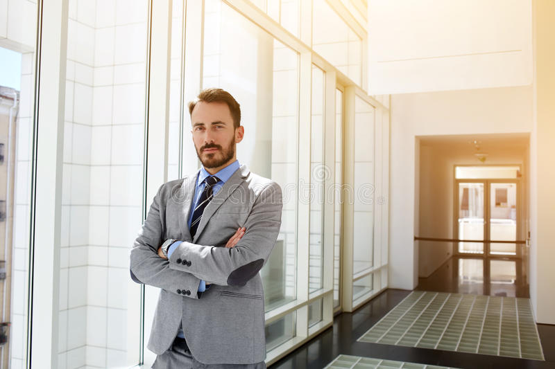 .Serious CEO is posing in corridor of his enterprise. Young man intelligent boss in corporate clothes is standing with crossed arms in modern office interior stock photos