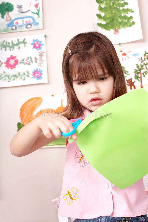 Serious child cutting paper. royalty free stock photo