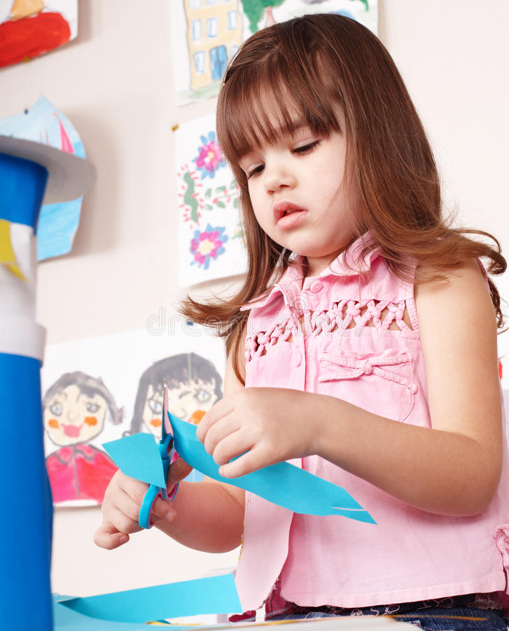 Serious child cutting paper. royalty free stock images