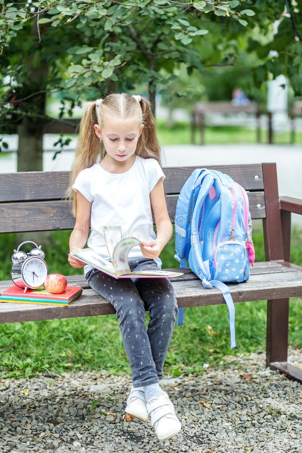 A serious child is reading a book on a bench. The concept of school, study, education, friendship, childhood. A serious child is reading a book on a bench. The royalty free stock photography