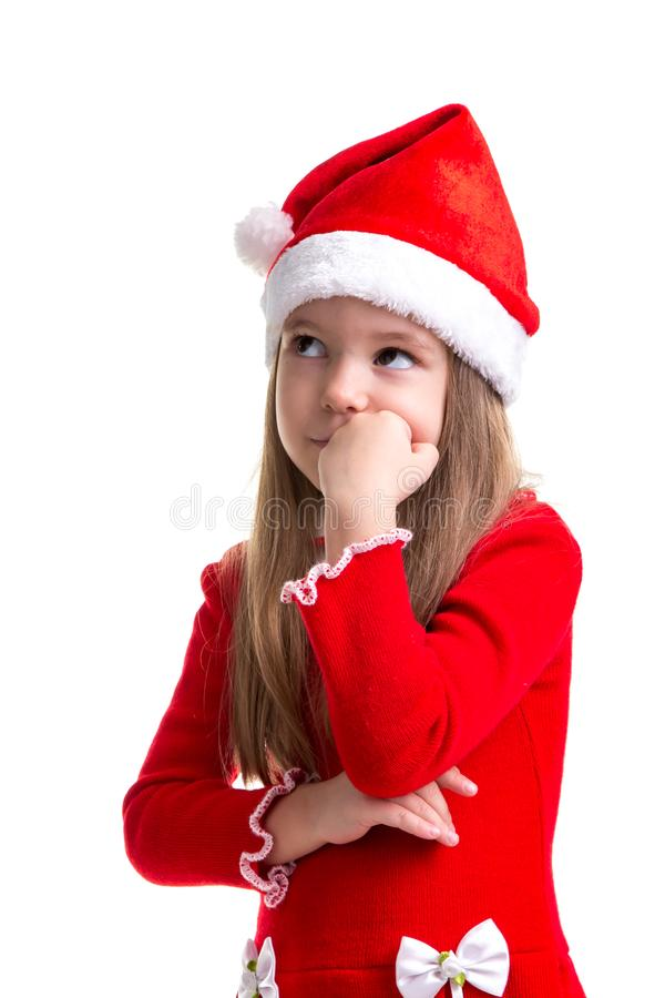 Serious christmas girl with the fist under the chin, looking up, wearing a santa hat isolated over a white background stock photography