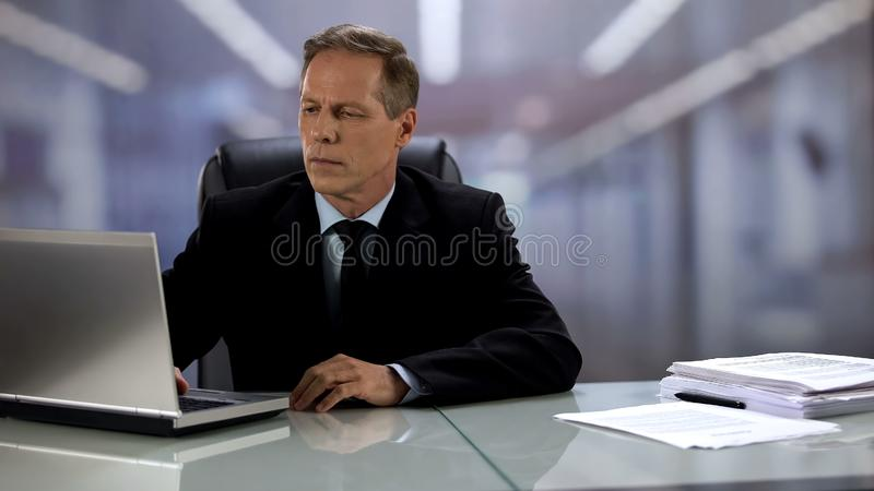 Serious company boss working at laptop, answering e-mail, professionalism royalty free stock photos