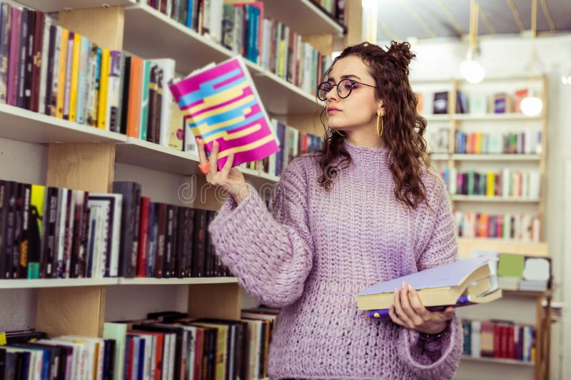 Serious concentrated girl carrying opened book in raised hand. Traveling through library. Serious concentrated girl carrying opened book in raised hand while stock photos