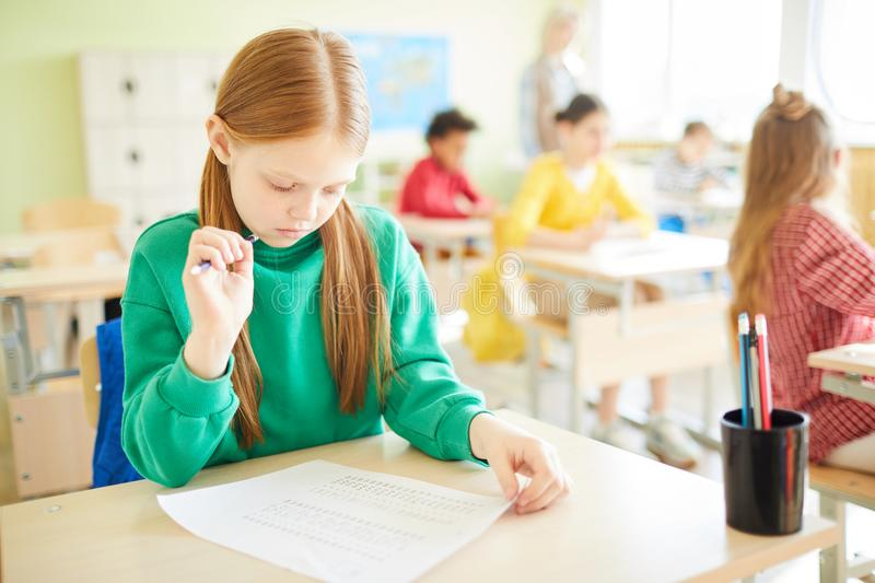 Concentrated girl checking test before turning in it stock images