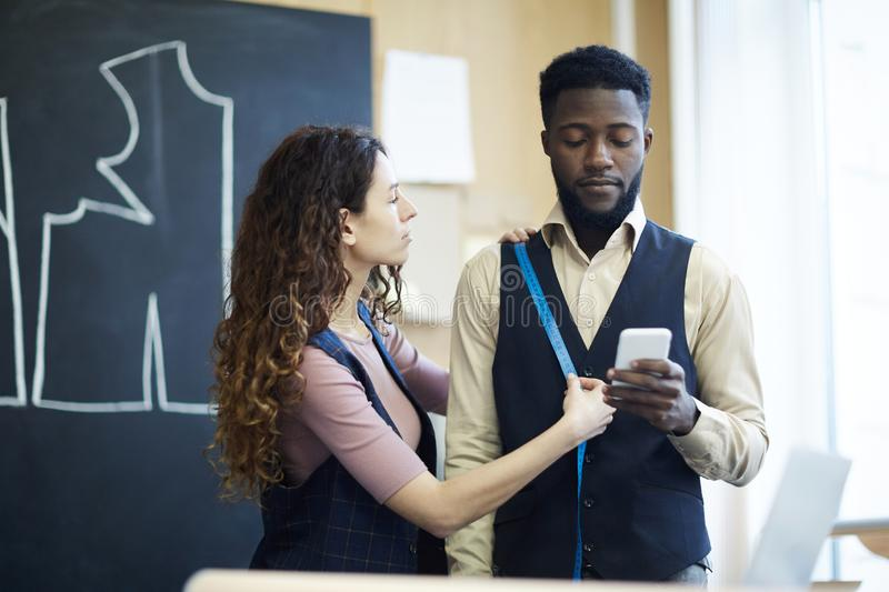 Lady tailor taking measures of black businessman with gadget royalty free stock photos