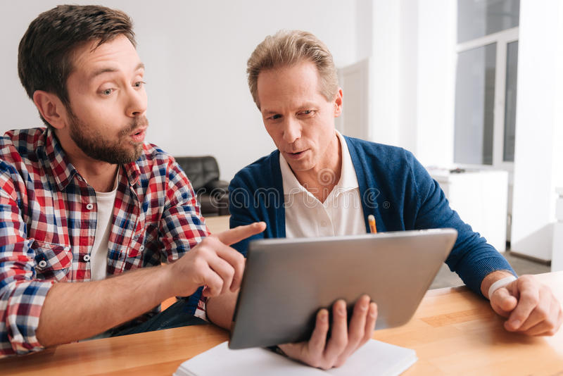 Serious concentrated man pointing at the tablet screen stock photography