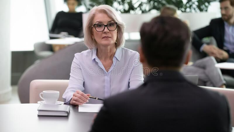 Serious middle aged female hr manager conducting interview with applicant. stock photography