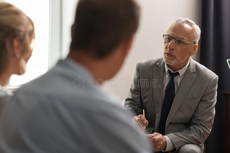 Serious concentrated psychoanalyst assessing his patients mental health stock photo
