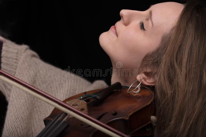 Passionate violin musician playing on black background. Serious and concentrated violin player - portrait of a woman on black background playing strings royalty free stock photography