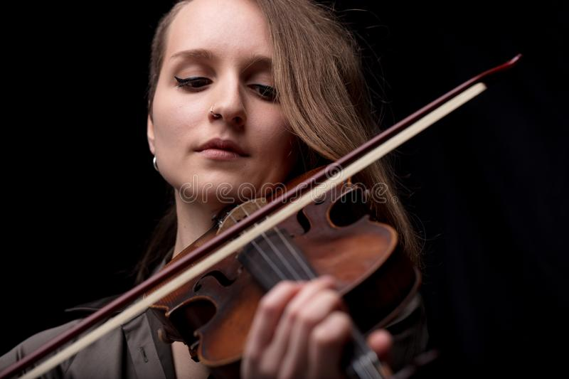 Passionate violin musician playing on black background royalty free stock images