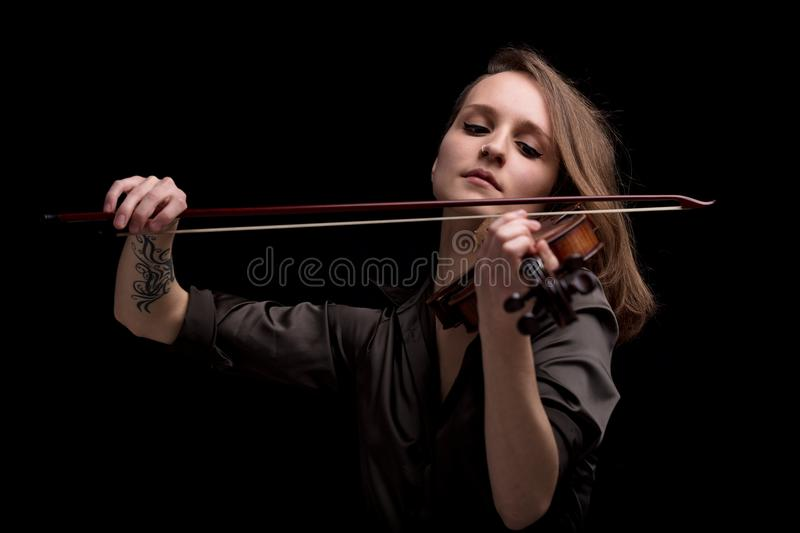 Passionate violin musician playing on black background royalty free stock photography