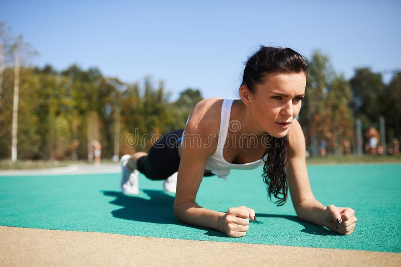 Concentrated lady doing plank at stadium stock image