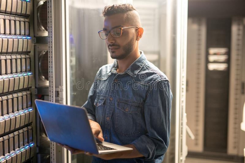Server specialist doing network monitoring. Serious concentrated young middle-eastern server specialist in glasses standing at network server and using portable stock photos