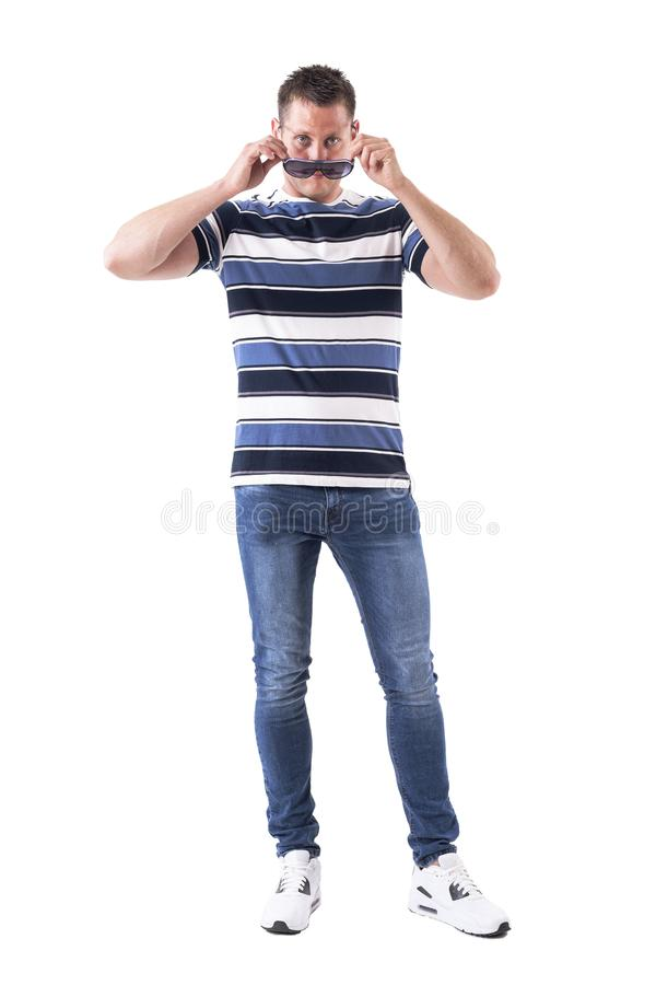 Serious confident adult man applying or taking off sunglasses with intense stare at camera. Full body isolated on white background stock image