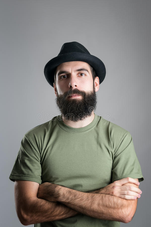 Serious confident bearded guy with crossed arms looking at camera stock photo