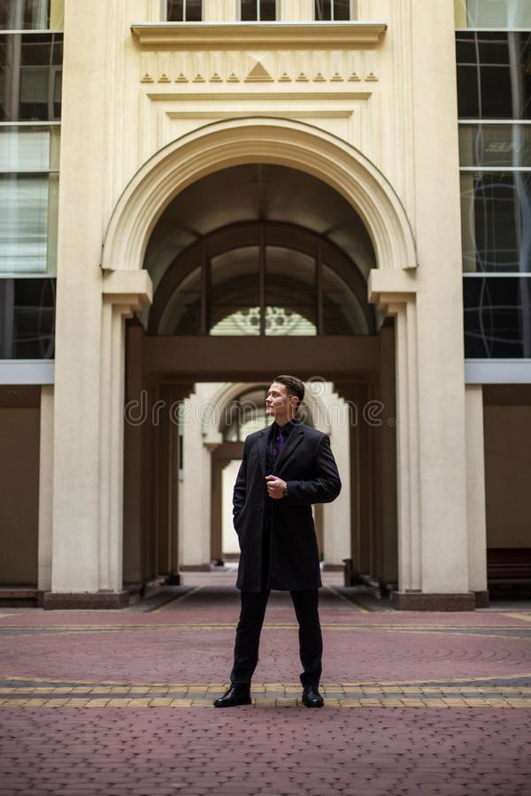 Serious and confident businessman looking away against the background of an old architectural arch royalty free stock photography