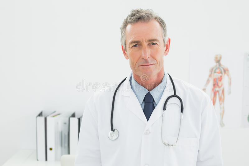 Serious confident male doctor at the medical office. Portrait of a serious confident male doctor standing in the medical office royalty free stock photography