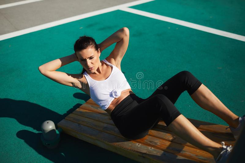 Doing twisting crunches. Serious confident sporty young woman sitting on wooden bench and doing twisting crunches at sports ground stock image