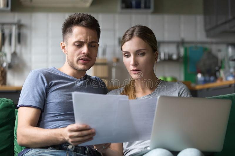 Serious confused couple checking domestic bills with papers and. Serious confused couple checking high domestic bills with papers and laptop, millennial family royalty free stock photography