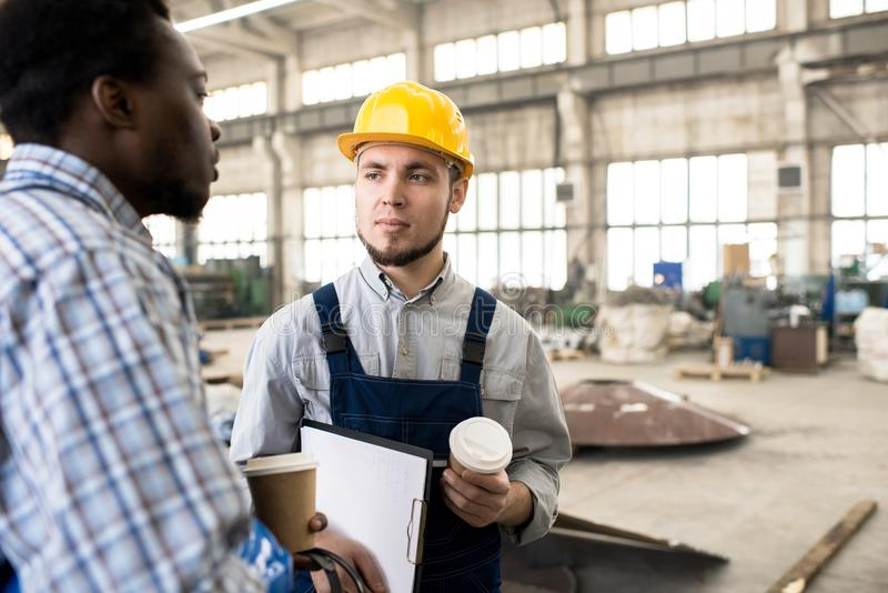 Serious construction colleagues making coffee break royalty free stock image