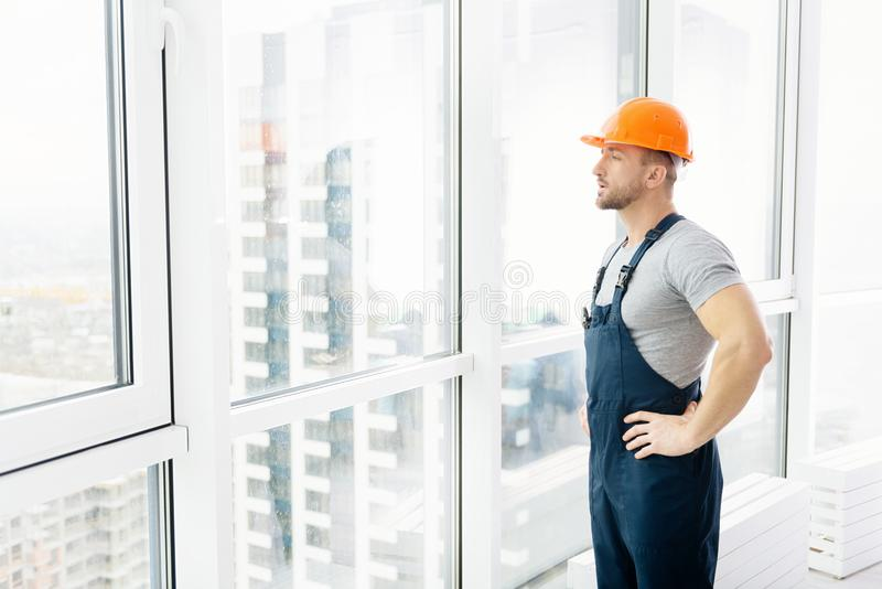 Serious construction engineer standing near window royalty free stock photos