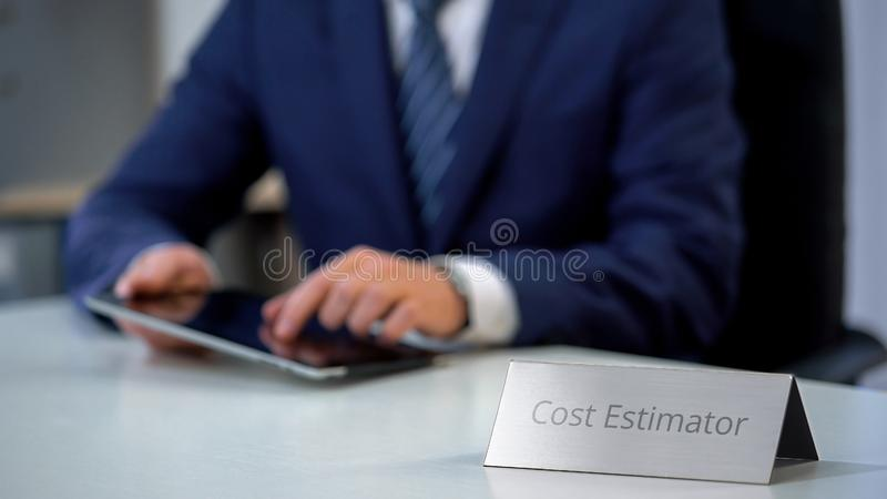Serious cost estimator working on tablet pc, loaning budget on work place. Stock photo stock photo