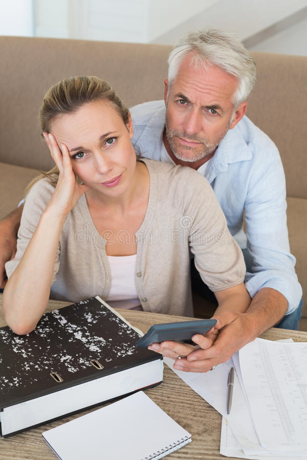 Serious couple calculating their bills at the couch stock images