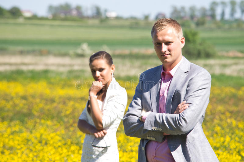 Serious couple in field of wildflowers royalty free stock photos