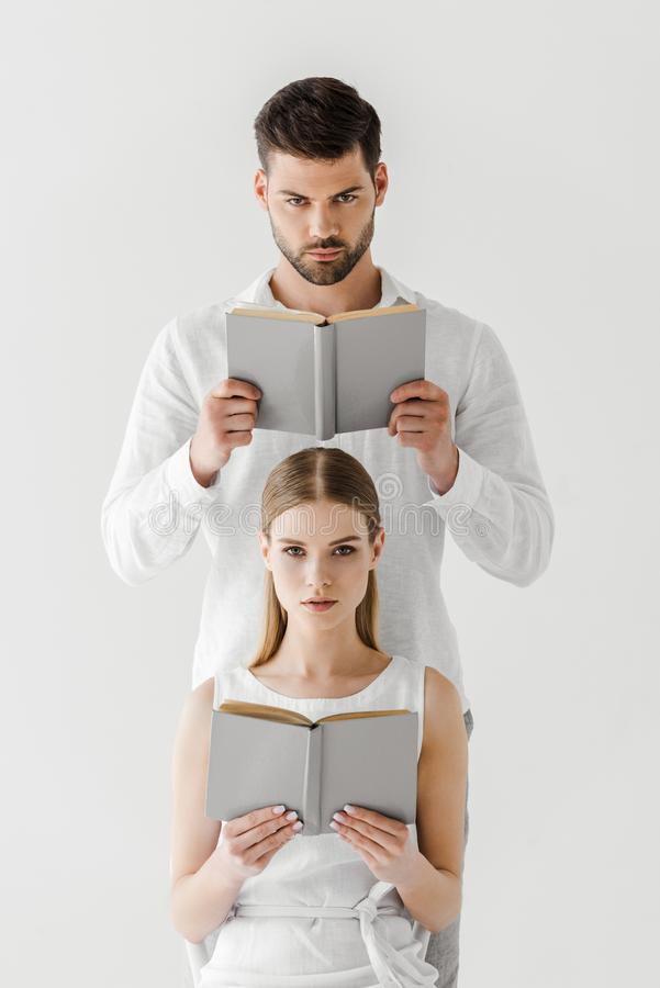 serious couple reading books isolated on grey stock photo