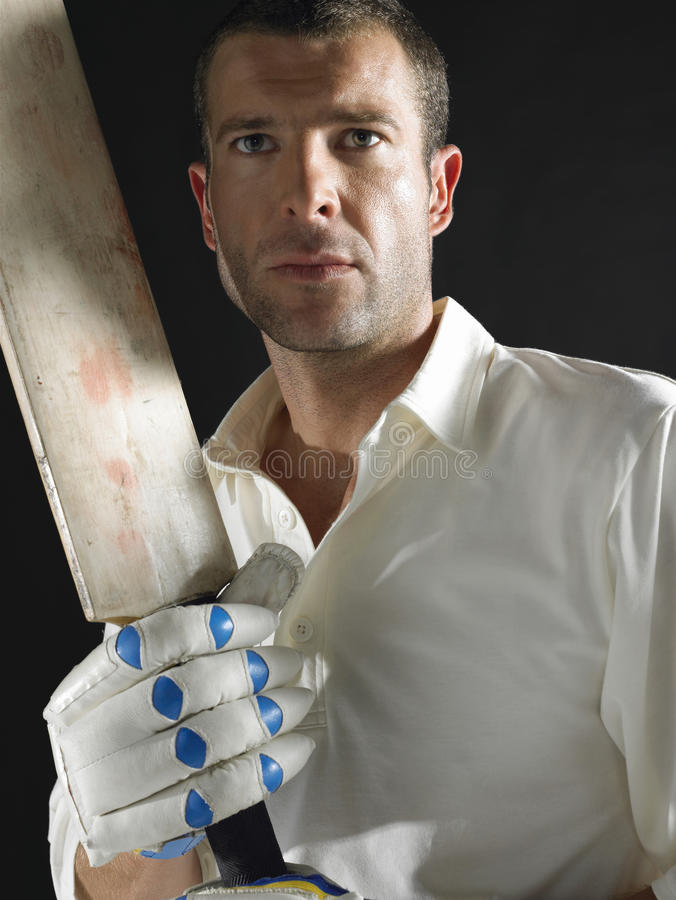 Serious Cricket Player With Bat. Serious young cricket player with bat against black background stock image