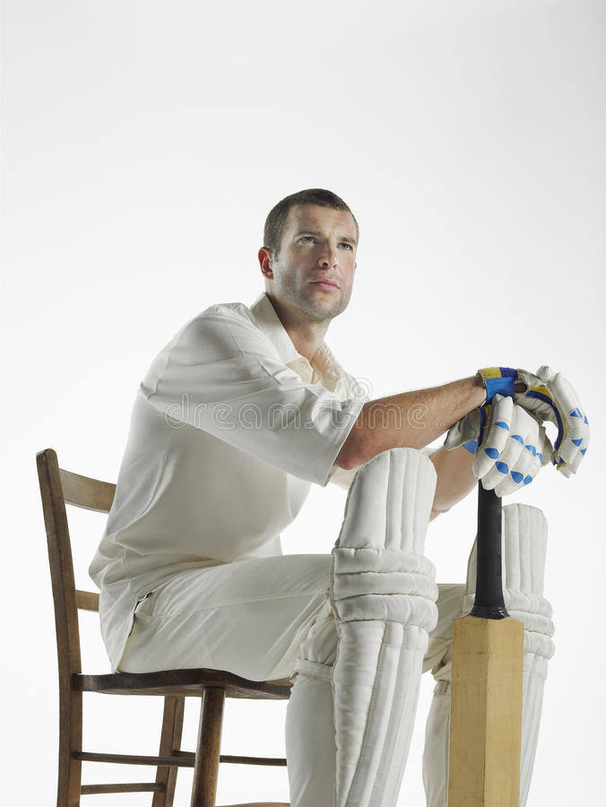 Serious Cricket Player Sitting With Bat. Serious young cricket player with bat sitting in chair against white background stock photo