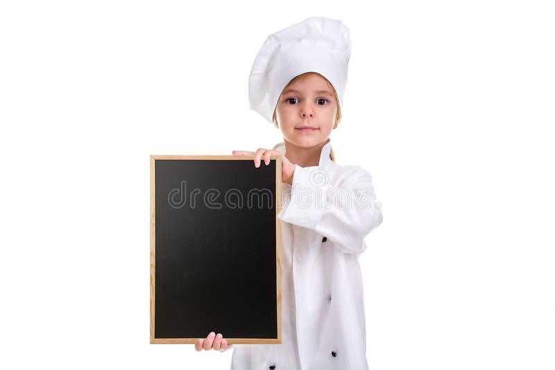 Serious cute girl chef white uniform isolated on white background. Girl with a floured face holding a menu black empty royalty free stock photo