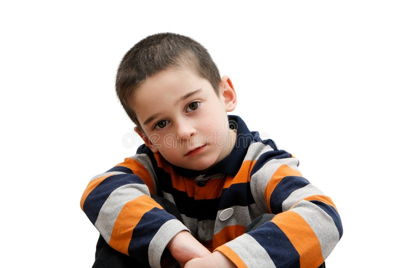 Serious cute little boy sits stock images