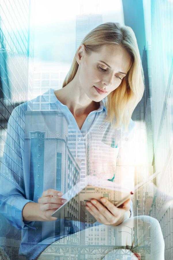 Serious deep lady sitting and reading her notebook. royalty free stock images