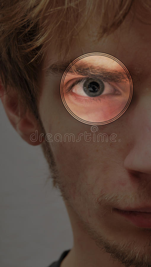 Serious determined young man eye scan stock photo