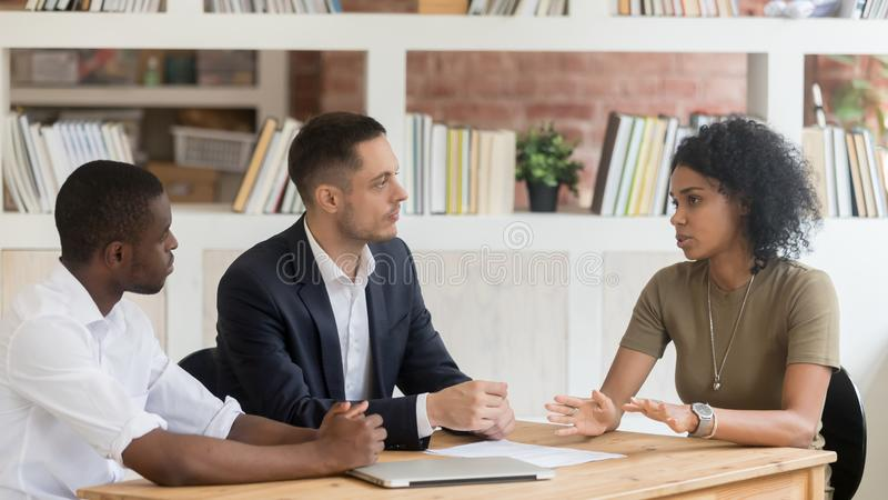 Serious diverse businesspeople sitting at table negotiating at business meeting royalty free stock photography