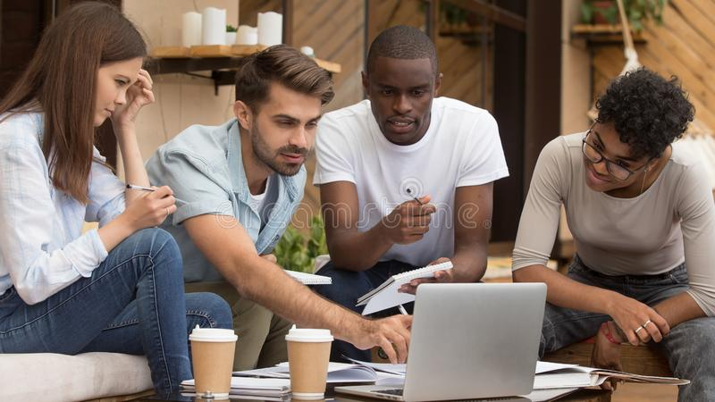 Serious diverse friends study together with laptop notebooks in cafe. Serious diverse friends study together with laptop and notebooks prepare for exam in cafe royalty free stock image