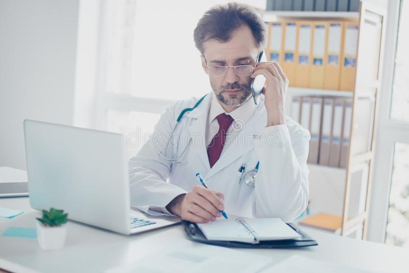Serious doctor is consulting patient by the phone and writing do. Wn the details. He is in a white coat, glasses, sitting in modern office royalty free stock photo