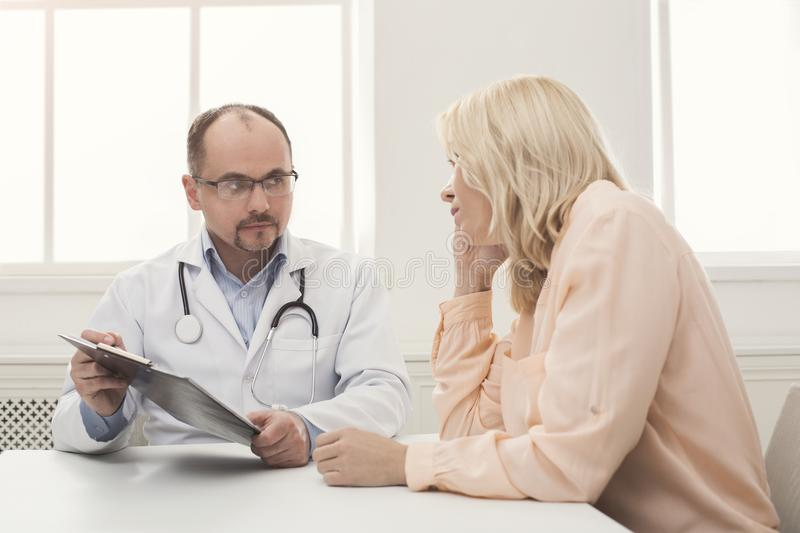 Doctor consulting woman in hospital royalty free stock images