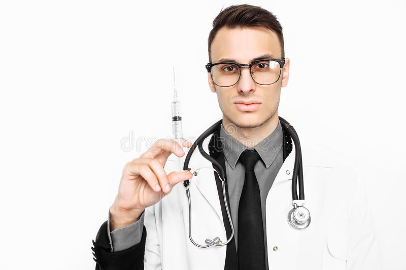 Serious doctor in glasses, with a stethoscope on his neck, holding a syringe for injection, isolated on a white background royalty free stock image